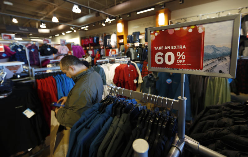 FILE - In this Dec. 24, 2018, photo a last-minute shopper scans his mobile device next to a sign marking discounts on coats at Columbia store at the Outlet Malls in Castle Rock in Castle Rock, Colo. Retailers and consumer product makers like American Textile may have received some short moment of reprieve after the Trump Administration delayed the 10% tariffs on some products which also include toys, clothing and shoes. (AP Photo/David Zalubowski, File)