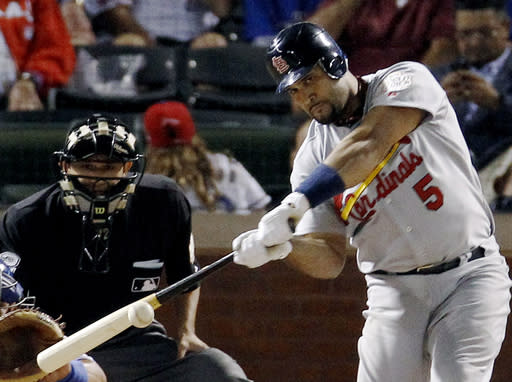 FILE - In this Oct. 22, 2011, file photo, St. Louis Cardinals' Albert Pujols hits a solo home run during the ninth inning of Game 3 of baseball's World Series against the Texas Rangers, in Arlington, Texas. Pujols was drafted in the 13th round in 1999. He was in the majors by 2001, when he won Rookie of the Year honors and drove in 130 runs. Three MVP awards later, Pujols is closing in on the end of his career with 656 home runs and counting. (AP Photo/Eric Gay, File)