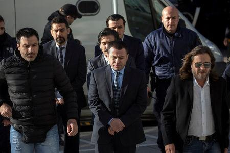 FILE PHOTO - Four of the eight Turkish soldiers, who fled to Greece in a helicopter and requested political asylum after a failed military coup against the government, line up as they are escorted by police officers at the Supreme Court in Athens