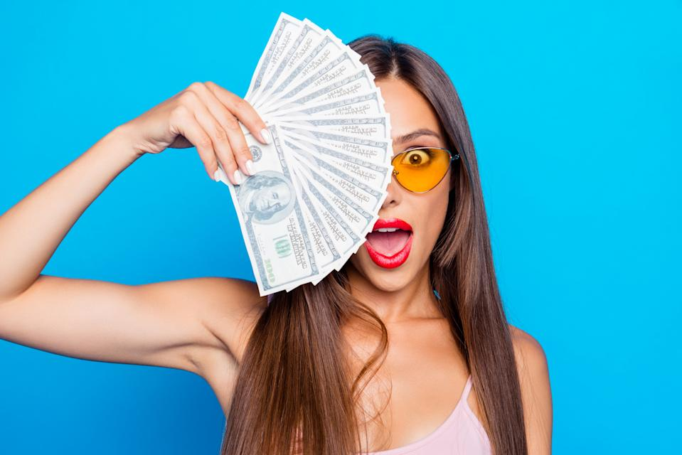 Portrait of nice sweet tender attractive adorable straight-haired girl wearing yellow sunglasses, opened mouth, covering half of face with fan of 100 usd, isolated over bright vivid blue background