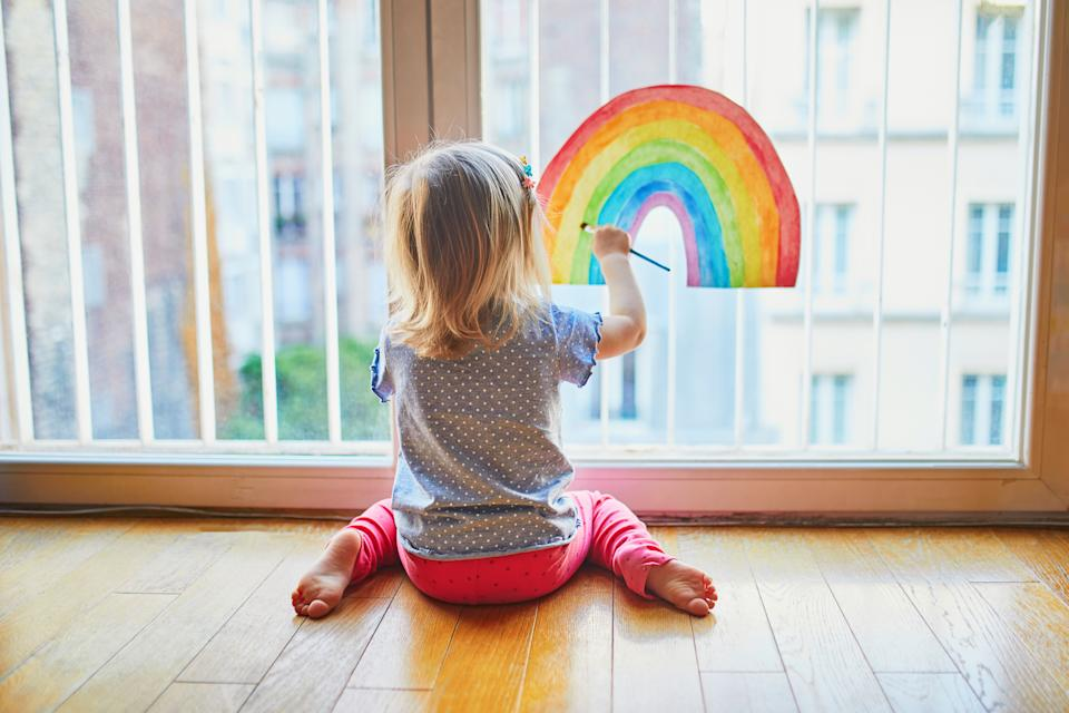 Adorable toddler girl painting rainbow on the window glass as sign of hope. Creative games for kids staying at home during lockdown. Self isolation and coronavirus quarantine concept