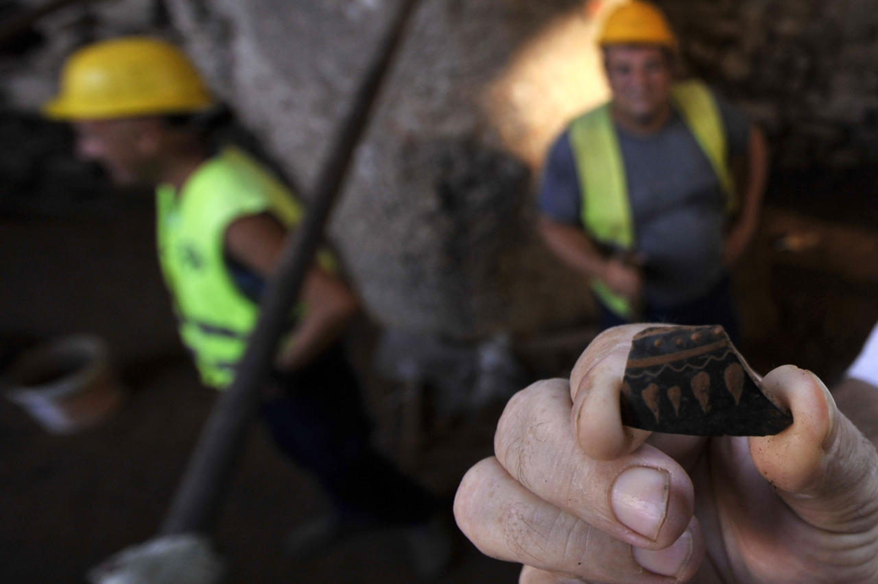 A worker of Metro's construction company holds a fragment of old pottery in the northern Greek port city of Thessaloniki on Monday, June 25, 2012. Archaeologists in Greece's second largest city have uncovered a 70-meter (230-foot) section of an ancient road built by the Romans that was city's main travel artery nearly 2,000 years ago. The marble-paved road was unearthed during excavations for the city's new subway system that is due to be completed in four years, and will be raised to be put on permanent display for passengers when the metro opens. (AP Photo/Nikolas Giakoumidis)