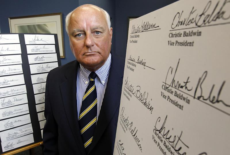 FILE - In this July 18, 2011 file photo, Salem, Mass. Registrar of Deeds John O'Brien stands near copies of robo-signed signatures at his office, in Salem, Monday, July 18, 2011. O'Brien said an investigation of more than 710,000 documents in his office found that 25,187 homeowners in the county, or about 3.5 percent, have paperwork on file with signatures he believes are fraudulent.  (AP Photo/Steven Senne, File)
