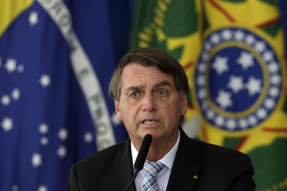 Brazilian President Jair Bolsonaro attends a ceremony to sign a law that expands the federal government's ability to acquire COVID-19 vaccines, at Planalto presidential palace in Brasilia, Brazil, Wednesday, March 10, 2021. (AP Photo/Eraldo Peres)