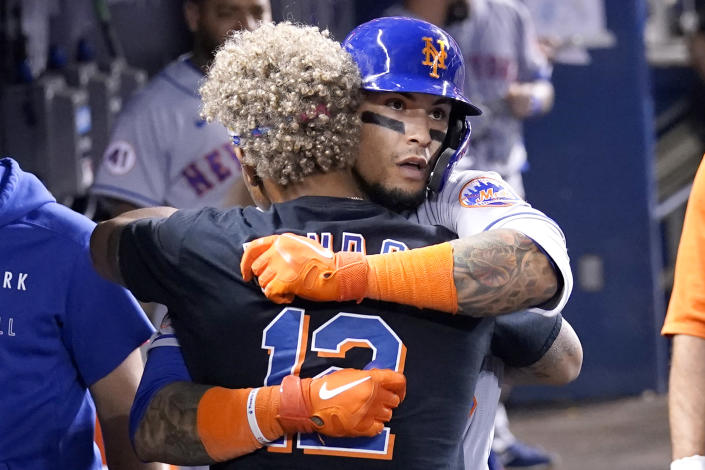 New York Mets' Javier Baez, right, hugs Francisco Lindor after hitting a solo home run during the eighth inning of a baseball game against the Miami Marlins, Wednesday, Aug. 4, 2021, in Miami. The Mets won 5-3. (AP Photo/Lynne Sladky)
