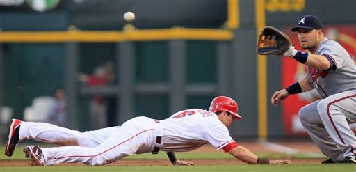 Cincinnati Reds' Drew Stubbs (6) dives safely back to first as Atlanta Braves first baseman Eric Hinske catches a pick-off throw from pitcher Randall Delgado in the third inning of a baseball game Thursday, May 24, 2012, in Cincinnati. (AP Photo/Al Behrman)