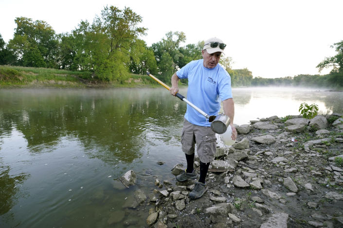 Des Moines Water Works employee Bill Blubaugh collects a water sample from the Raccoon River, Thursday, June 3, 2021, in Des Moines, Iowa. Each day the utility analyzes samples from the Raccoon River and others from the nearby Des Moines River as it works to deliver drinking water to more than 500,000 people in Iowa's capital city and its suburbs. (AP Photo/Charlie Neibergall)