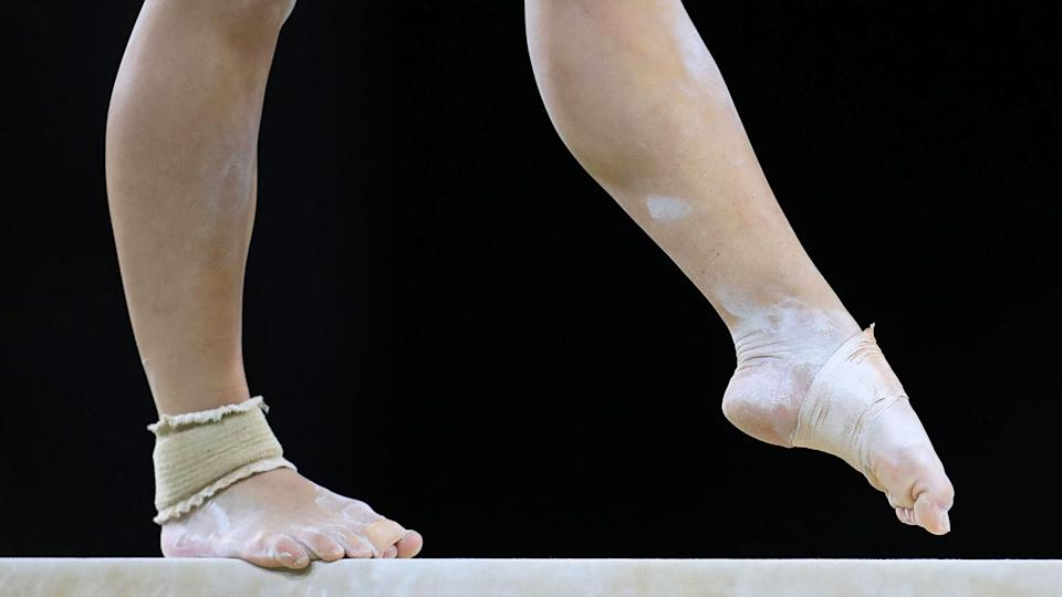 Pictured here, an Australian gymnast performs on the beam in competition.