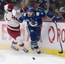 Vancouver Canucks' Christopher Tanev (8) avoids a check from Carolina Hurricanes' Andrei Svechnikov, of Russia, during the first period of an NHL hockey game in Vancouver, British Columbia, Thursday Dec. 12, 2019. (Darryl Dyck/The Canadian Press via AP)
