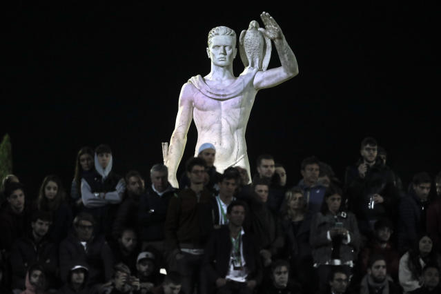One of the statues by sculptor Eugenio Baroni adorns the Pietrangeli tennis stadium behind spectators watching a match at the Italian Open tennis tournament, in Rome, Thursday, May 16, 2019. The tennis stadium is part of the Foro Italico sports complex, which was initially called Foro Mussolini (Mussolini's Forum). It was built under Benito Mussolini's regime to bolster Rome's bid for the 1944 Olympics, which never took place. (AP Photo/Andrew Medichini)