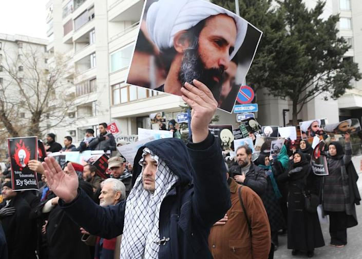 Iranian and Turkish demonstrators hold pictures of Shiite cleric Sheikh Nimr al-Nimr as they protest outside the Saudi Embassy in Ankara, on January 3, 2016 (AFP Photo/Adem Altan)