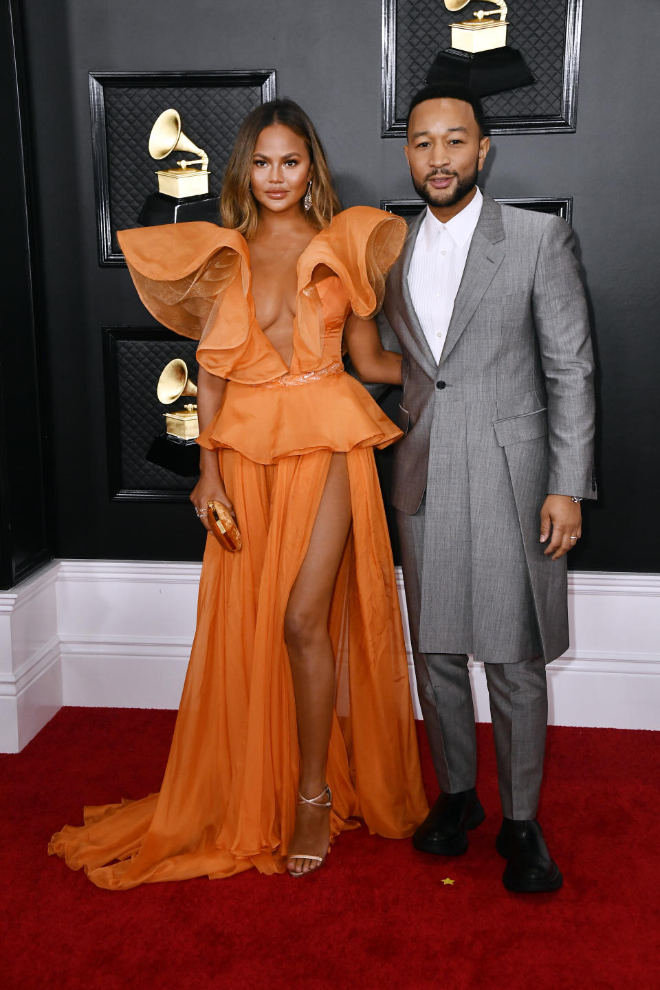 """Teigan brought the glamour to the red carpet to support her husband and Grammy nominee, John Legend. The """"Cravings"""" author and model was a tangerine dream in a ruffled gown with thigh-high slit. Not to be outdone, Legend flexed his fashion muscles in a steel grey suit with an asymmetrical hem."""