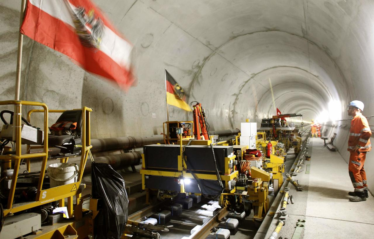 An Austrian and a German national flag fly on mobile machinery during the installation of the railway tracks in the NEAT Gotthard Base tunnel near Erstfeld May 7, 2012. Crossing the Alps, the world's longest train tunnel should become operational at the end of 2016. The project consists of two parallel single track tunnels, each of a length of 57 km (35 miles) REUTERS/Arnd Wiegmann   (SWITZERLAND - Tags: BUSINESS CONSTRUCTION EMPLOYMENT TRAVEL)