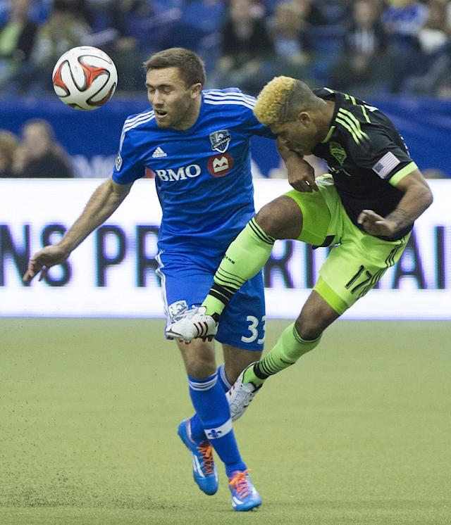 Montreal Impact's Andrew Wenger, left, challenges Seattle Sounders' DeAndre Yedlin for the ball during second half MLS soccer action in Montreal, Sunday, March 23, 2014. (AP Photo/The Canadian Press, Graham Hughes)