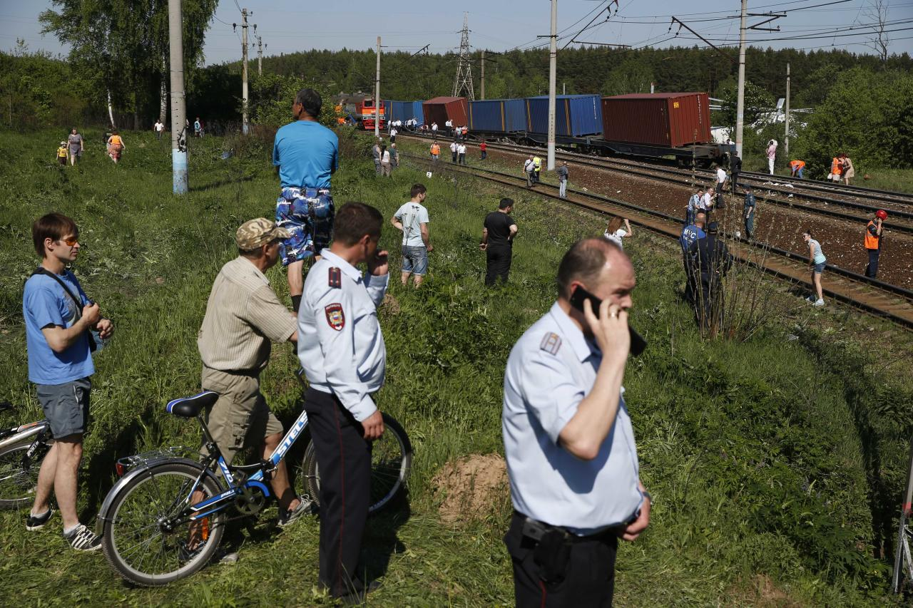 Russian Emergency Ministry employees examine the site of train collision near the city of Naro-Fominsk outside Moscow. The Interior Ministry said the accident happened when several cars of a cargo train derailed and hit a passenger train near Naro-Fominsk, a town 50 kilometers (30 miles) southwest of Moscow. There were fatalities in the crash and tens of people were injured. (AP Photo/ Pavel Golovkin)