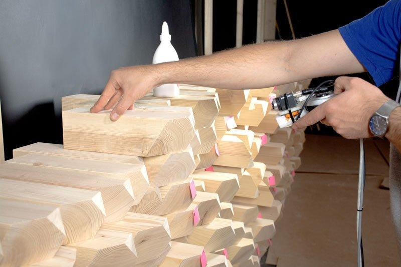 Carpenters use robotic cameras to properly assemble a modular acoustic timber wall