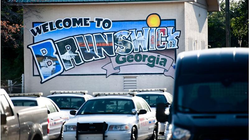 Mural saying Welcome to Brunswick Georgia with police cars in front