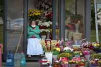 A flower vendor with a mask for protection against the COVID-19 infection, partially covering her face watches people passing by in Bucharest, Romania, Friday, Sept. 18, 2020. (AP Photo/Andreea Alexandru)
