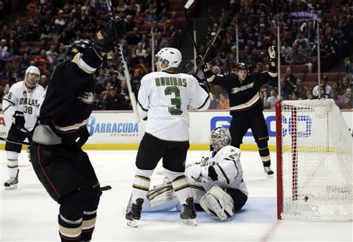 Dallas Stars goalie Kari Lehtonen, center right, and Stephane Robidas, center left, watch as Anaheim Ducks' Teemu Selanne, front, of Finland, and Corey Perry celebrate a goal by Selanne during the second period of an NHL hockey game in Anaheim, Calif., Wednesday, April 3, 2013. (AP Photo/Jae C. Hong)