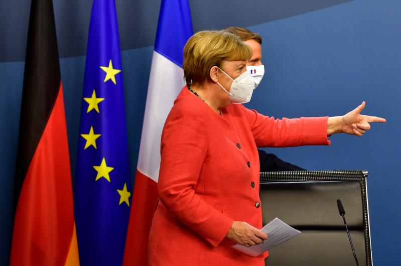 TOPSHOT - German Chancellor Angela Merkel (L) and French President Emmanuel Macron (R) step onstage for a joint press conference at the end of the European summit at the EU headquarters in Brussels on July 21, 2020. - EU leaders approved a 750-billion-euro package to revive their coronavirus-ravaged economies after a tough 90-hour summit on July 21, along with a trillion-euro budget for the next seven years. (Photo by JOHN THYS / POOL / AFP) (Photo by JOHN THYS/POOL/AFP via Getty Images)