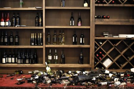 Fallen wine bottles are seen at Cult Following Wine Bar after an earthquake in Napa, California August 24, 2014. REUTERS/Stephen Lam
