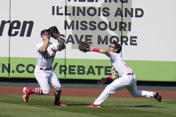 St. Louis Cardinals left fielder Tyler O'Neill, left, catches a fly ball by Cincinnati Reds' Eugenio Suarez as Cardinals center fielder Scott Hurst reaches in during the ninth inning of a baseball game Sunday, April 25, 2021, in St. Louis. (AP Photo/Jeff Roberson)