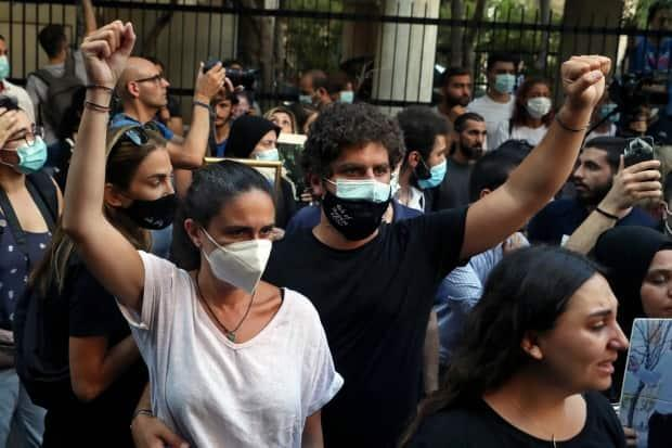 Tracy and Paul Naggear raise their fists during a protest outside the home of caretaker Interior Minister Mohamed Fehmi in Beirut on July 13, 2021. (Bilal Hussein/The Associated Press - image credit)