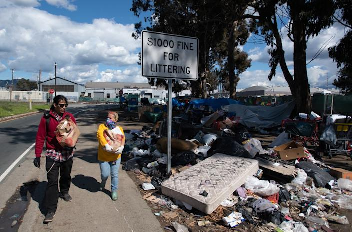 """Andrea Henson, right, walks with a homeless man who helps her deliver supplies to people living in a homeless encampment along a freeway in Emeryville, Calif., on March 26. <span class=""""copyright"""">(Josh Edelson / For The Times)</span>"""