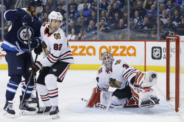 Chicago Blackhawks goaltender J-F Berube (34) makes a save as Winnipeg Jets left wing Kyle Connor (81) and Blackhawks defenseman Jordan Oesterle (82) watch during the second period of an NHL hockey game Thursday, March 15, 2018, in Winnipeg, Manitoba. (John Woods/The Canadian Press via AP)