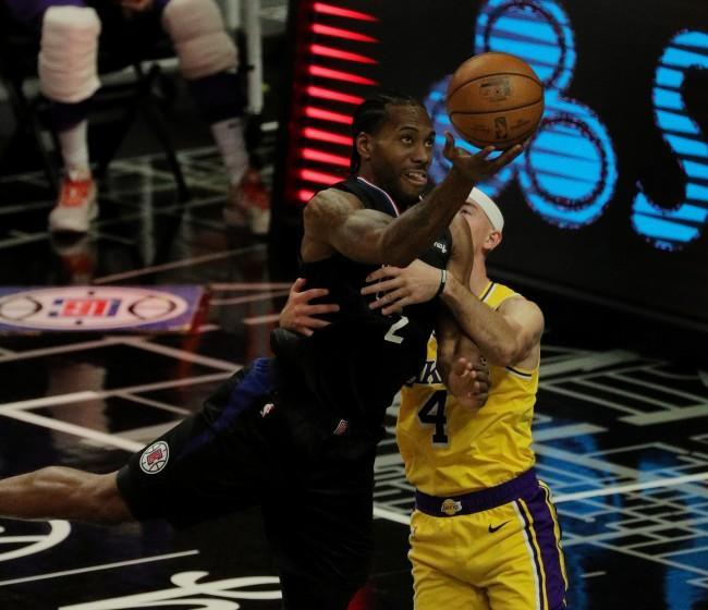 LOS ANGELES, CA - MAY 6, 2021: LA Clippers forward Kawhi Leonard (2) is fouled by Los Angeles Lakers guard Alex Caruso (4) as he drives to the basket in the second half at Staples Center on May 6, 2021 in Los Angeles, California.(Gina Ferazzi / Los Angeles Times)