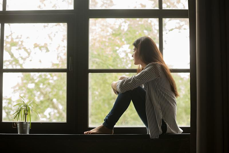 Young woman sitting on a ledge and looking out a window.