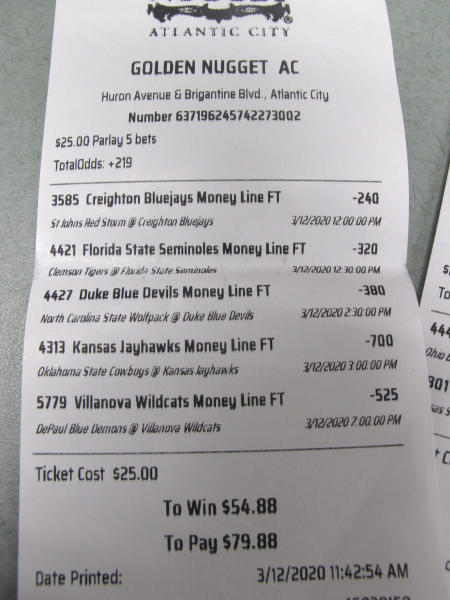 This March 12, 2020, shows a sports betting ticket at the Golden Nugget casino in Atlantic City, N.J. where all five games that were bet on were canceled due to coronavirus precautions. Most professional and college sports events in the U.S. have been suspended or delayed, leaving little to bet on. For most people, the new coronavirus causes only mild or moderate symptoms. For some it can cause more severe illness.(AP Photo/Wayne Parry)
