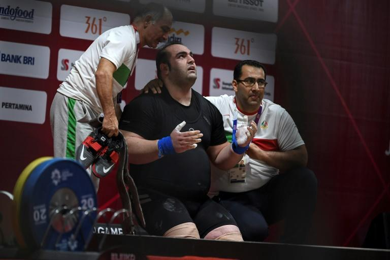 Iran's Behdad Salimikordasiabi (C) reacts as he competes in the men's +105kg weightlifting event during the 2018 Asian Games in Jakarta on August 27, 2018