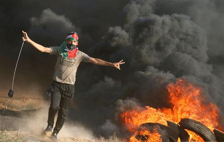 A Palestinian holds a sling to hurl stones at Israeli troops during a protest calling for lifting the Israeli blockade on Gaza and demand the right to return to their homeland, at the Israel-Gaza border fence, east of Gaza City September 14, 2018. REUTERS/Mohammed Salem