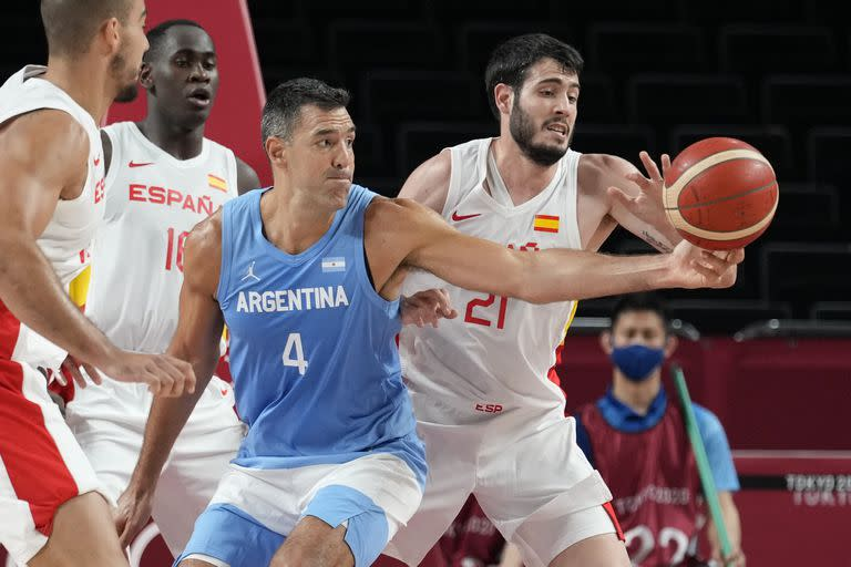 Spain's Alejandro Abrines Redondo (21) tries to steal the ball from Argentina's Luis Scola (4) during a men's basketball preliminary round game at the 2020 Summer Olympics, Thursday, July 29, 2021, in Saitama, Japan. (AP Photo/Eric Gay)