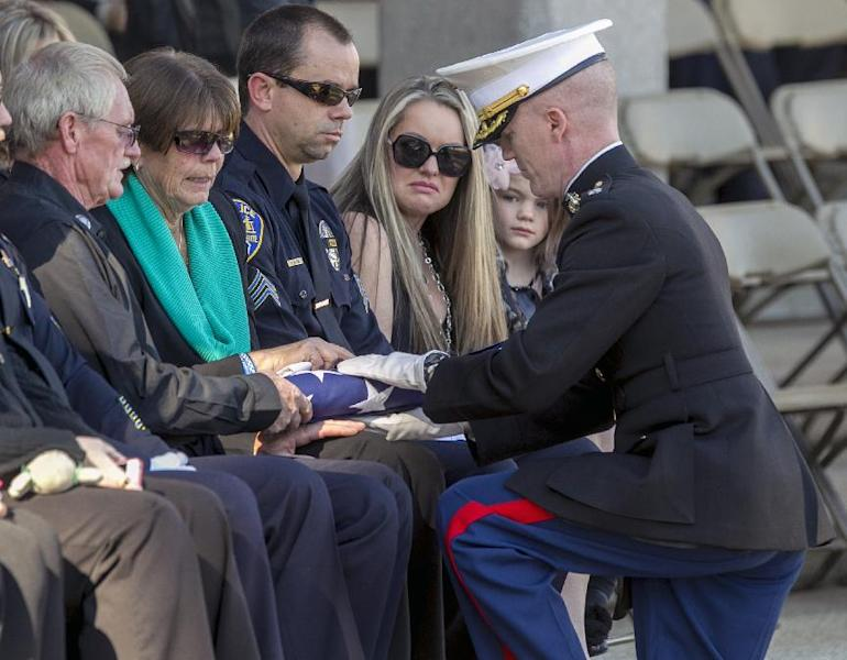 CORRECTS ID'S - A U.S. Marine presents presents the flag to the parents of slain police officer Michael Crain, from left, Stephen and Cynthia Crain, as Regina Crain, widow of Michael Crain, and their daughter Kaitlyn, look on during a committal service at the Riverside National Cemetery in Riverside, Calif., Wednesday, Feb. 13, 2013. Crain was mortally wounded on Feb. 7 in an ambush shooting as he sat in a police car at a stoplight. Ex-Los Angeles police officer Christopher Dorner is charged in Crain's death. (AP Photo/Damian Dovarganes)