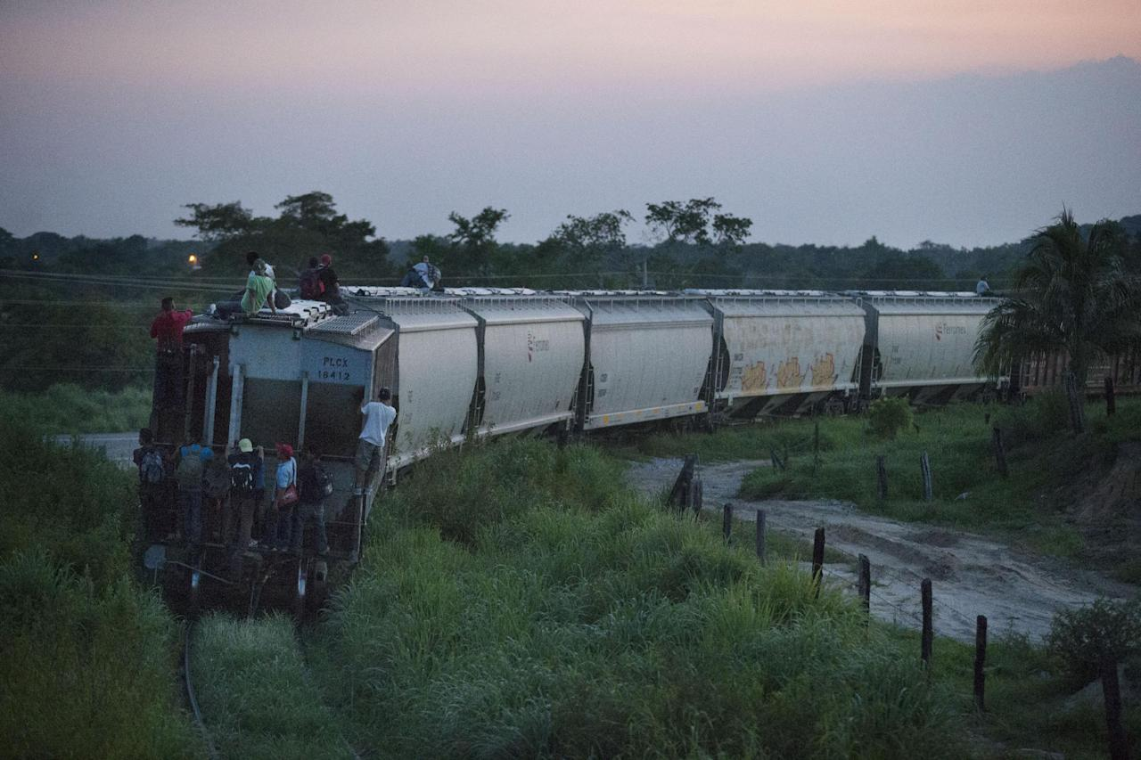 "In this Aug. 26, 2014 photo, a handful of Central American migrants cling to a northbound freight train after jumping aboard outside Arriaga, Mexico. A Mexican crackdown seems to be keeping women and children off the deadly train, known as ""The Beast,"" that has traditionally helped thousands of migrants head north. (AP Photo/Rebecca Blackwell)"
