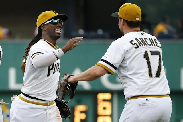 Pittsburgh Pirates' Andrew McCutchen, left, celebrates with teammate Gaby Sanchez, right, as they run off the field after a 5-3 won over the Colorado Rockies in a baseball game in Pittsburgh Sunday, July 20, 2014.(AP Photo/Gene J. Puskar)