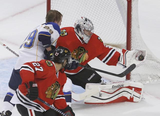 Chicago Blackhawks goalie Corey Crawford (50) makes a glove save on a shot by St. Louis Blues center Steve Ott (29) as Johnny Oduya (27) watches during the first period in Game 3 of a first-round NHL hockey Stanley Cup playoff series game Monday, April 21, 2014, in Chicago. (AP Photo/Charles Rex Arbogast)
