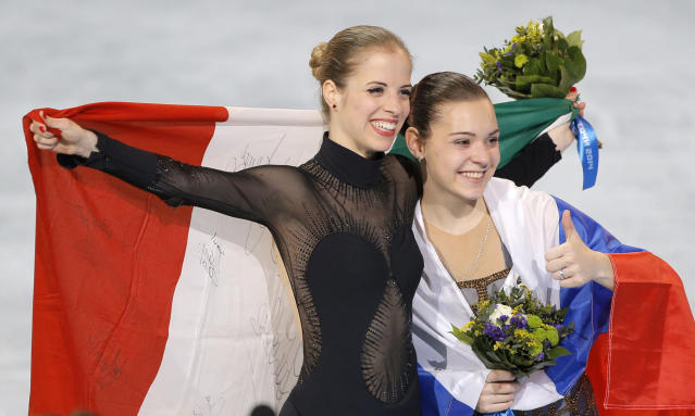 Adelina Sotnikova of Russia, right, and Carolina Kostner of Italy celebrate with their national flags as they pose for photographers following the flower ceremony for the women's free skate figure skating final at the Iceberg Skating Palace during the 2014 Winter Olympics, Thursday, Feb. 20, 2014, in Sochi, Russia. Sotnikova placed first, followed by Kim and Kostner. (AP Photo/Vadim Ghirda)