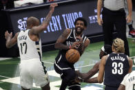 Brooklyn Nets' Kyrie Irving controls the ball as he drives between Milwaukee Bucks' P.J. Tucker (17) and Jrue Holiday during the first half of an NBA basketball game Tuesday, May 4, 2021, in Milwaukee. (AP Photo/Aaron Gash)