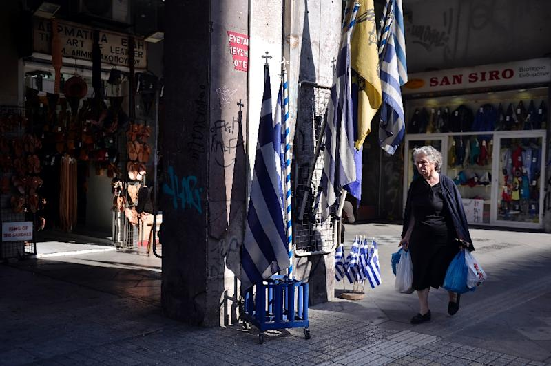 A woman walks by Greek national flags at the Athens central market on June 9, 2015 (AFP Photo/Louisa Gouliamaki)