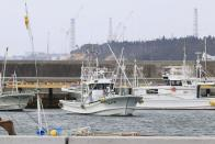 Fishing boats are seen at Ukedo port with a backdrop of Fukushima Daiichi nuclear power plant in Namie town, Fukushima prefecture, northeastern Japan, Tuesday, April 13, 2021, Japan's government decided Tuesday to start releasing massive amounts of treated radioactive water from the wrecked Fukushima nuclear plant into the Pacific Ocean in two years - an option fiercely opposed by local fishermen and residents. (Yusuke Ogata/Kyodo News via AP)