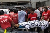 EDITORS NOTE: Graphic content / Edhi volunteers move the body of an alleged gunman from outside the Pakistan Stock Exchange building in Karachi on June 29, 2020. - At least six people were killed after gunmen attacked the Pakistan Stock Exchange in Karachi on June 29, police said, with one policeman among the dead after the assailants opened fire and hurled a grenade at the trading floor. (Photo by - / AFP) (Photo by -/AFP via Getty Images)