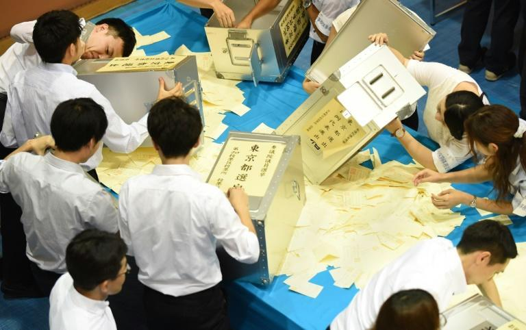 Officials open ballot boxes to count votes cast for Japan's upper house election at an electoral office in Tokyo