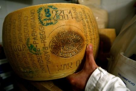 FILE PHOTO: An Italian grocer shows off his Parmesan cheese inside a shop in Rome