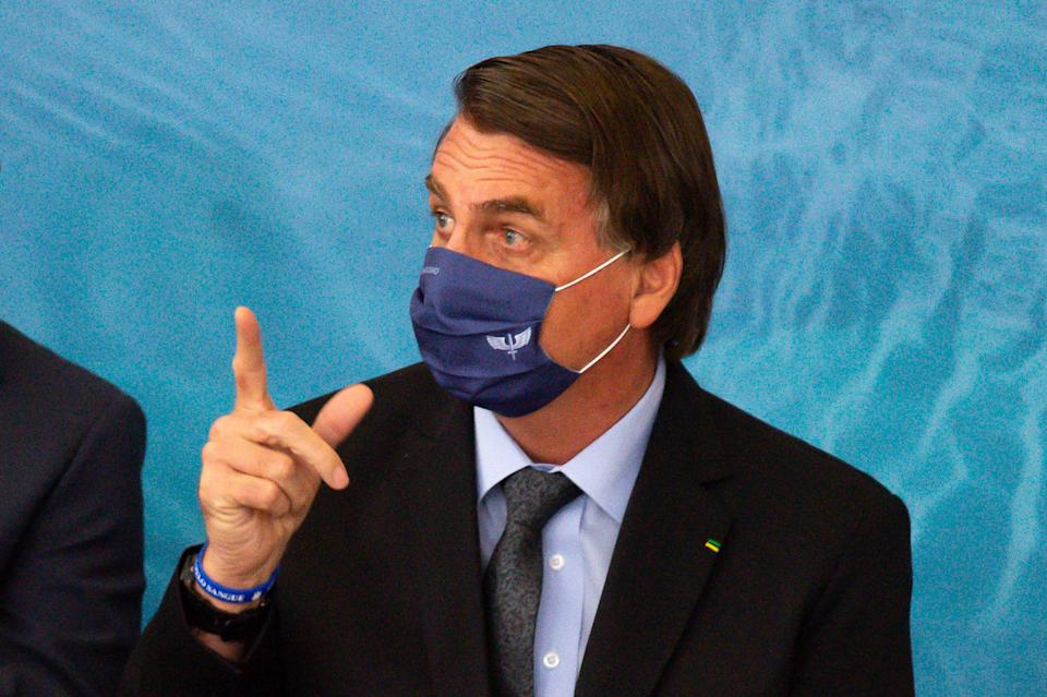 BRASILIA, BRAZIL - MARCH 22: President of Brazil Jair Bolsonaro gestures during the launch of Programa Aguas Brasileiras amidst the coronavirus (COVID-19) pandemic at the Planalto Palace on March 22, 2021 in Brasilia. Brazil has over 12.047,000 confirmed positive cases of Coronavirus and has over 295,425 deaths. (Photo by Andressa Anholete/Getty Images)