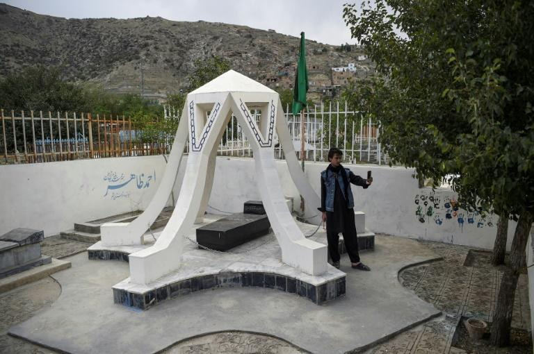 A visitor takes a selfie with his phone at the tomb of Ahmad Zahir, known as Afghanistan's Elvis Presley, at the Shuhada cemetery in Kabul