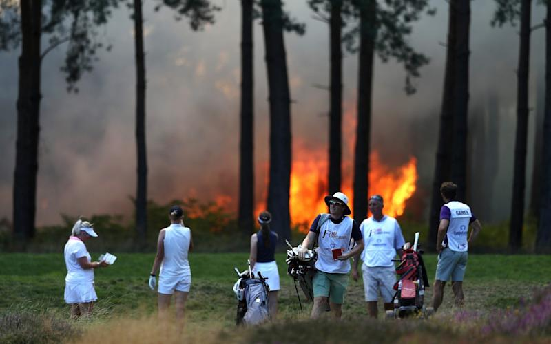 Players, Sophie Powell, Cara Gainer and Gabriella Cowley and their caddies look on as a fire nears the 10th hole during day three of The Rose Ladies Series on The West Course in the first ever ladies professional event at Wentworth Golf Club - GETTY IMAGES