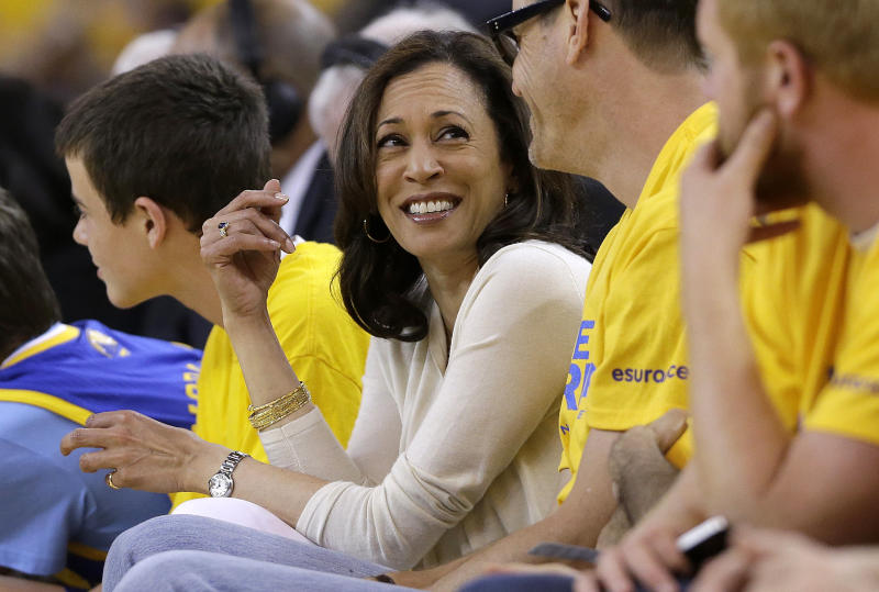 Kamala Harris shown surrounded by fans in yellow shirts at a basketball game.
